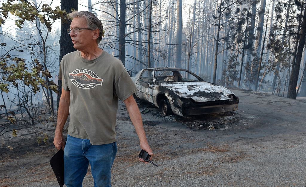 . Jon Cunningham looks at the destruction near where his house burned in Oakhurst, Calif., Sunday, Sept. 14, 2014, as two raging wildfires in the state forced hundreds of people to evacuate their homes.  (AP Photo/The Fresno Bee, Mark Crosse)