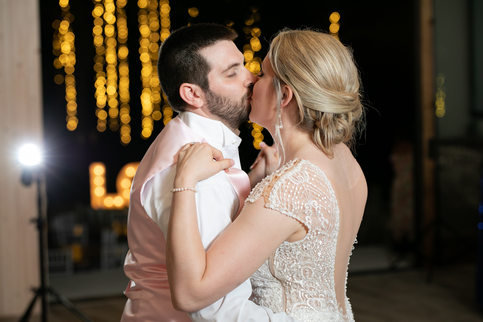 bride and groom kissing as they dance at ther wedding reception