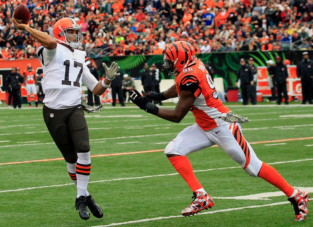 . Cleveland Browns quarterback Jason Campbell (17) is pursued by Cincinnati Bengals defensive end Carlos Dunlap (96) in the first half of an NFL football game, Sunday, Nov. 17, 2013, in Cincinnati. (AP Photo/Tom Uhlman)