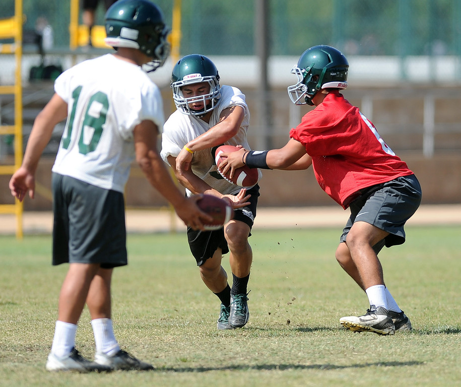 . QB Garrett Fonseca, right, hands off during morning practice at South Hills High School on Friday, Aug. 9, 2013 in West Covina, Calif.   (Keith Birmingham/Pasadena Star-News)