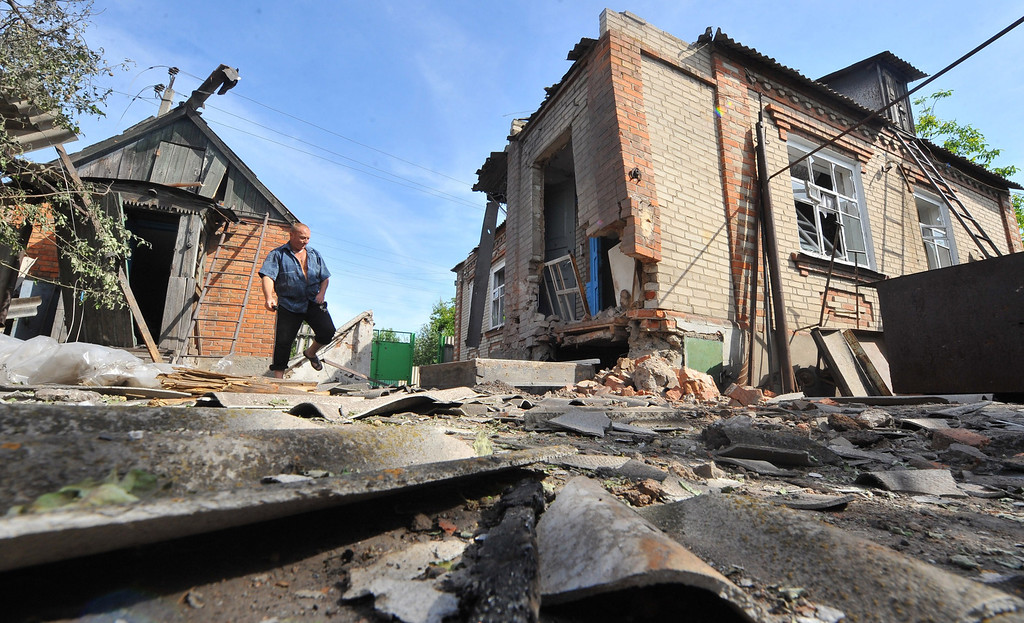 . A local resident walks by a house destroyed during a night combat between Ukrainian troops and armed pro-Russian militants in the village of Semenovka, near the eastern Ukrainian city of Slavyansk, on May 23, 2014. AFP PHOTO/ VIKTOR DRACHEV/AFP/Getty Images