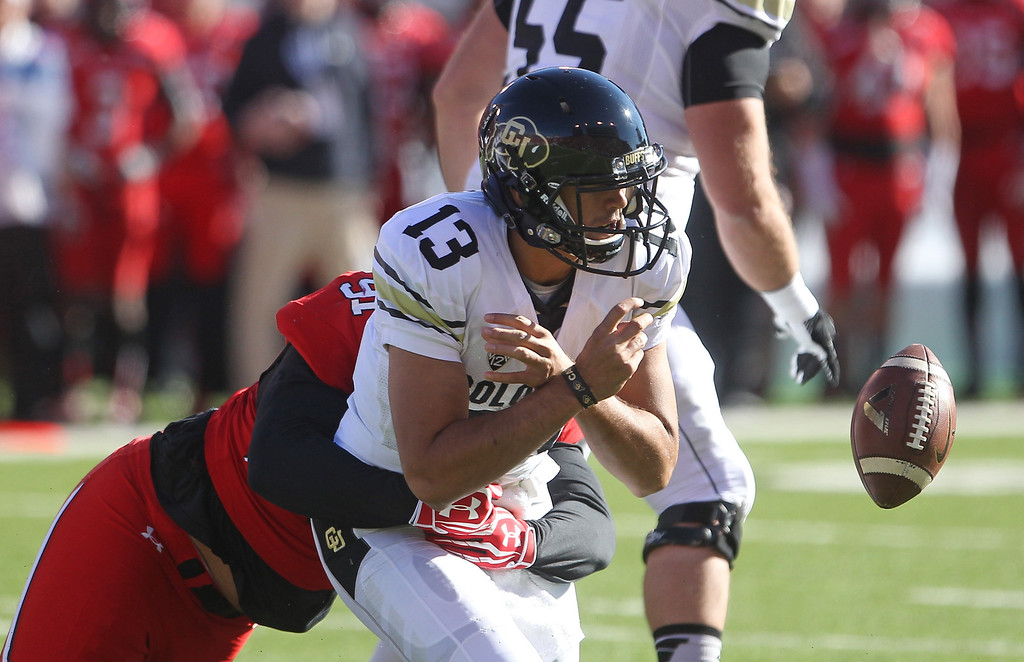 . Colorado quarterback Sefo Liufau (13) fumbles the ball as he is sacked by Utah defensive tackle Tenny Palepoi (91) in the first quarter during an NCAA college football game Saturday, Nov. 30, 2013, in Salt Lake City. (AP Photo/Rick Bowmer)