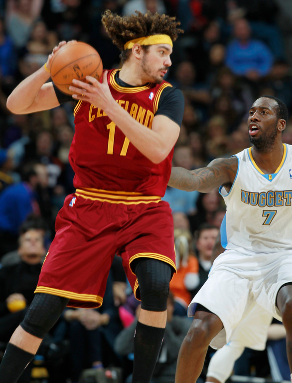 . Cleveland Cavaliers center Anderson Varejao, left, of Brazil, pulls in a loose ball as Denver Nuggets forward J.J. Hickson covers in the fourth quarter of an NBA basketball game in Denver, Friday, Jan. 17, 2014. The Cavaliers won 117-109. (AP Photo/David Zalubowski)