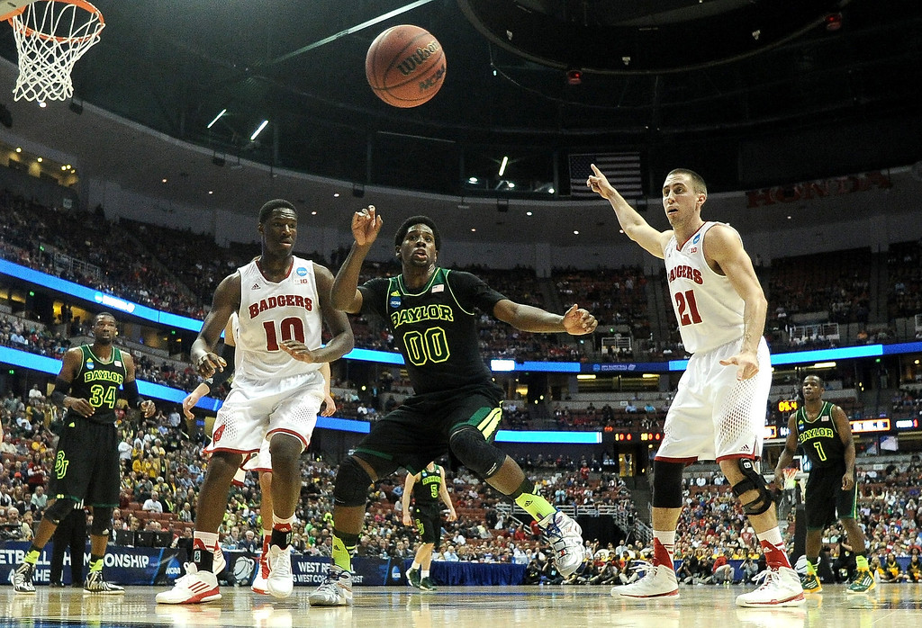 . Royce O\'Neale #00 of the Baylor Bears and Nigel Hayes #10 and Josh Gasser #21 of the Wisconsin Badgers look at a loose ball in the first half during the regional semifinal of the 2014 NCAA Men\'s Basketball Tournament at the Honda Center on March 27, 2014 in Anaheim, California.  (Photo by Harry How/Getty Images)