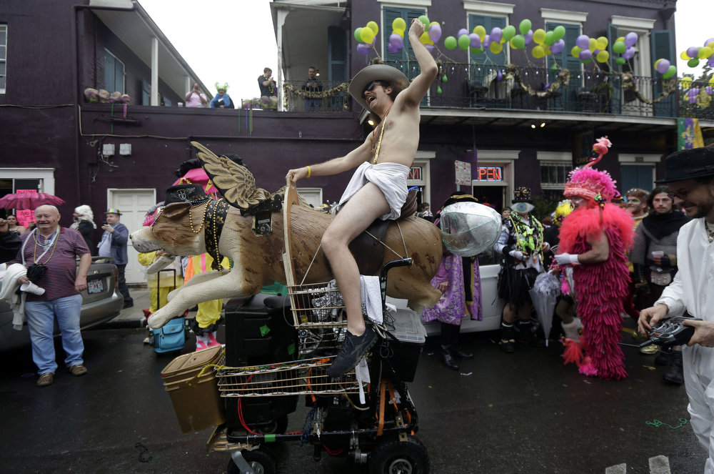 Description of . A man dressed in a diaper rides a mechanical dog with wings in the French Quarter during Mardi Gras in New Orleans, Tuesday, Feb. 12, 2013.  Despite threatening skies, the Mardi Gras party carried on as thousands of costumed revelers cheered glitzy floats with make-believe monarchs in an all-out bash before Lent.   Crowds were a little smaller than recent years, perhaps influenced by the forecast of rain. Still, parades went off as scheduled even as a fog settled over the riverfront and downtown areas. (AP Photo/Gerald Herbert)