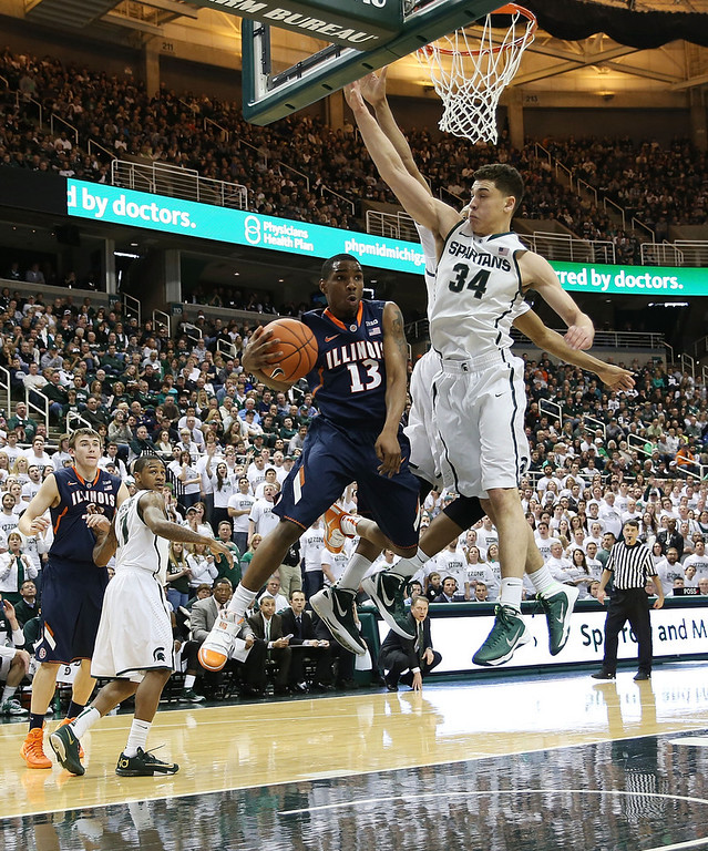 . Tracy Abrams #13 of the University of Illinois drives the ball to the basket as Gavin Schilling #24 of the Michigan State Spartans defends during the first half of the game at Breslin Center on March 1, 2014 in East Lansing, Michigan.  (Photo by Leon Halip/Getty Images)