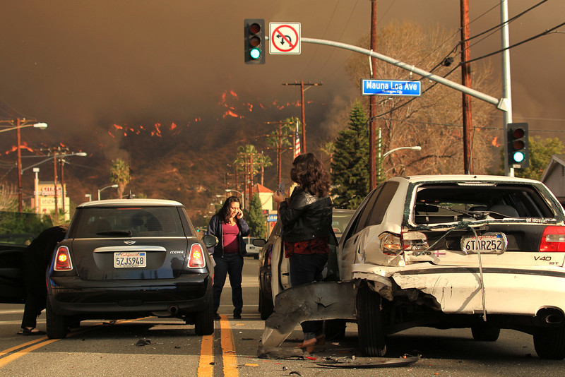 . Motorists exchange information after a car accident as a wildfire burns in the hills just north of the San Gabriel Valley community of Glendora, Calif. on Thursday, Jan 16, 2014. Southern California authorities have ordered the evacuation of homes at the edge of a fast-moving wildfire burning in the dangerously dry foothills of the San Gabriel Mountains. (AP Photo/Ringo H.W. Chiu)