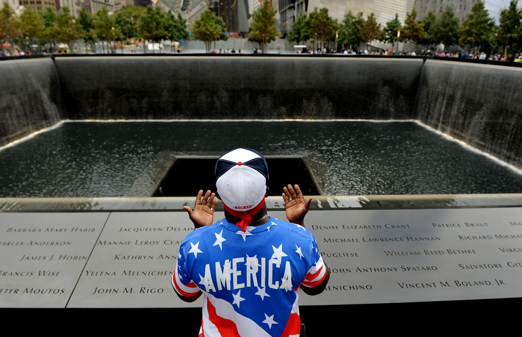 . Albert Biatta, of Queens section of New York prays while standing front of the inscribed name of his uncle Antoine Biatta at the edge of the North Pool during memorial observances on the 13th anniversary of the Sept. 11 terror attacks on the World Trade Center in New York, Thursday, Sept. 11, 2014. (AP Photo/Justin Lane, Pool)
