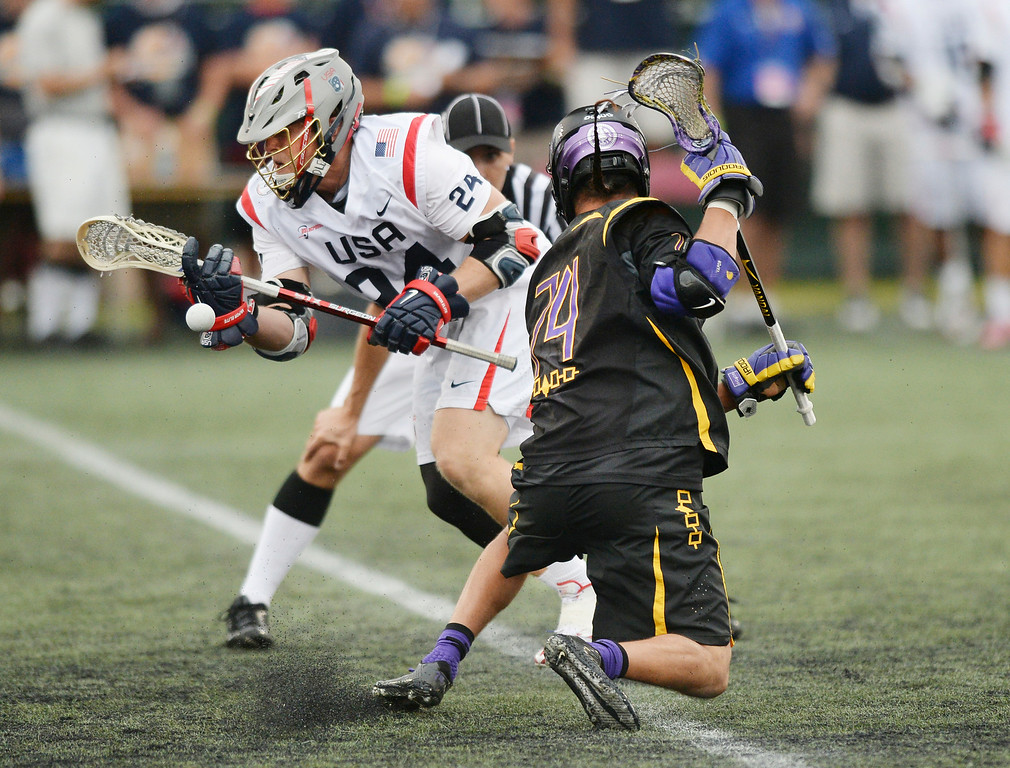 . United States midfielder Chris Eck (24) won a face-off with Iroquois midfielder Jeremy Thompson (74) in the first half.  Photo by Karl Gehring/The Denver Post