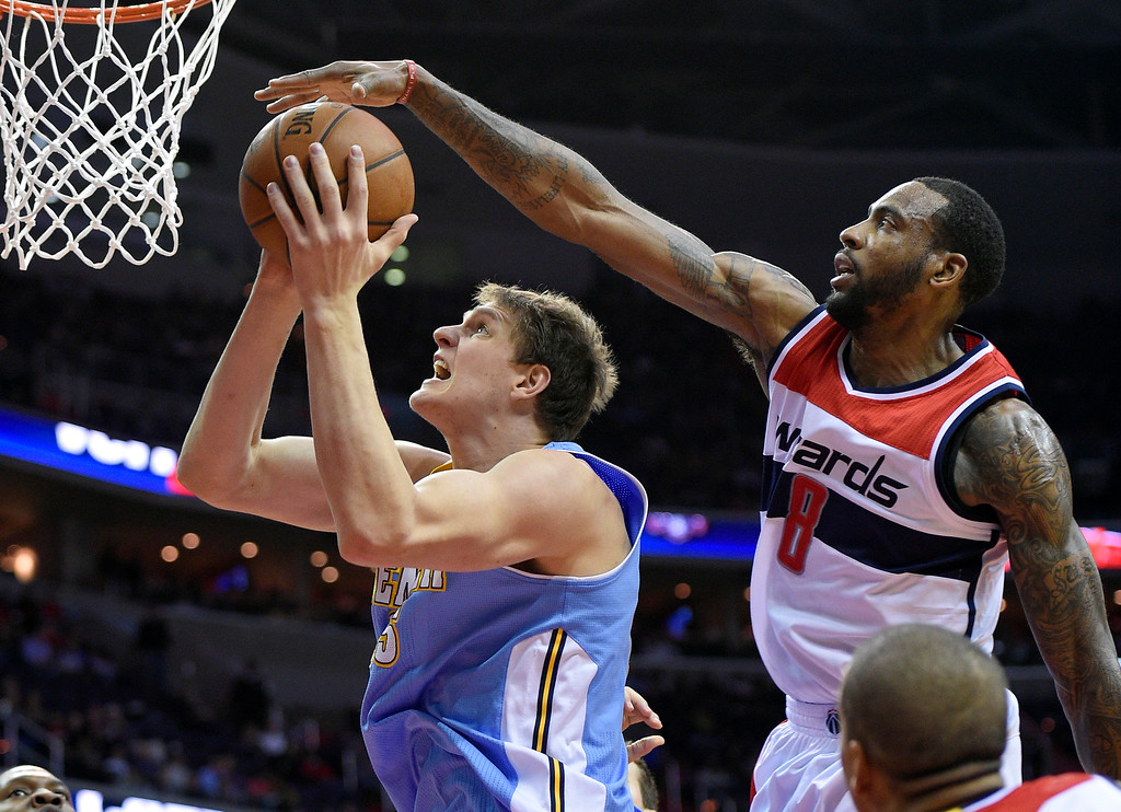 . Denver Nuggets center Timofey Mozgov, left, of Russia, goes to the basket against Washington Wizards forward Rasual Butler (8) during the first half of an NBA basketball game, Friday, Dec. 5, 2014, in Washington. (AP Photo/Nick Wass)