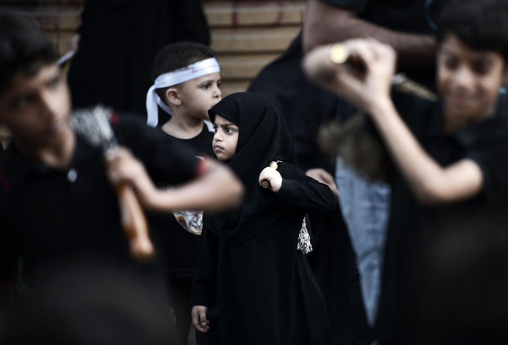 . Bahraini Shiite Muslim children take part in a ceremony marking Ashura, which commemorates the seventh century slaying of Imam Hussein, the grandson of Prophet Mohammed, in the village of Sanabis, west of Manama on November 1, 2014. MOHAMMED AL-SHAIKH/AFP/Getty Images
