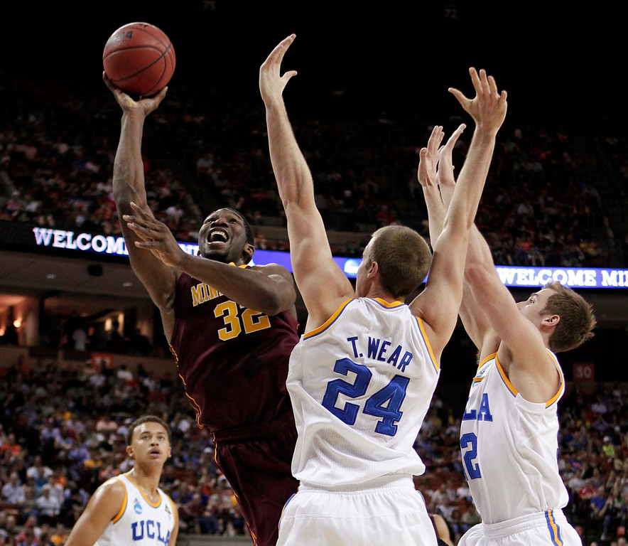 . University of Minnesota forward Trevor Mbakwe (L-R) shoots against University of California Los Angeles forward Travis Wear and forward David Wear during the first half of their second round NCAA basketball game in Austin, Texas March 22, 2013.   REUTERS/Mike Stone