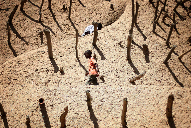 . Children walk on the Askia mausoleum, built in 1495  in Gao, northern Mali, Friday Feb. 15, 2013, one week after  a suicide bomber on a motorcycle killed himself attempting to blow up an army checkpoint at the entrance of the town. (AP Photo/Jerome Delay)