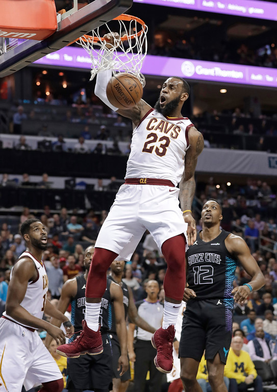 . Cleveland Cavaliers\' LeBron James (23) dunks past Charlotte Hornets\' Dwight Howard (12) during the second half of an NBA basketball game in Charlotte, N.C., Wednesday, March 28, 2018. (AP Photo/Chuck Burton)