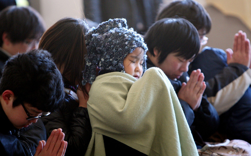 . Children pray during a memorial ceremony to commemorate the second anniversary of the March 11, 2011 earthquake and tsunami disasters in Kamaishi, Iwate prefecture on March 11, 2013. Japan on March 11 marked the second anniversary of a ferocious tsunami that claimed nearly 19,000 lives and sparked the worst nuclear accident in a generation.  JIJI PRESS/AFP/Getty Images