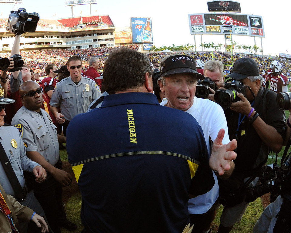 . Coach Steve Spurrier of the South Carolina Gamecocks greets coach Brady Hoke of the Michigan Wolverines after play in the Outback Bowl January 1, 2013 at Raymond James Stadium in Tampa, Florida.  South Carolina won 33 - 28. (Photo by Al Messerschmidt/Getty Images)
