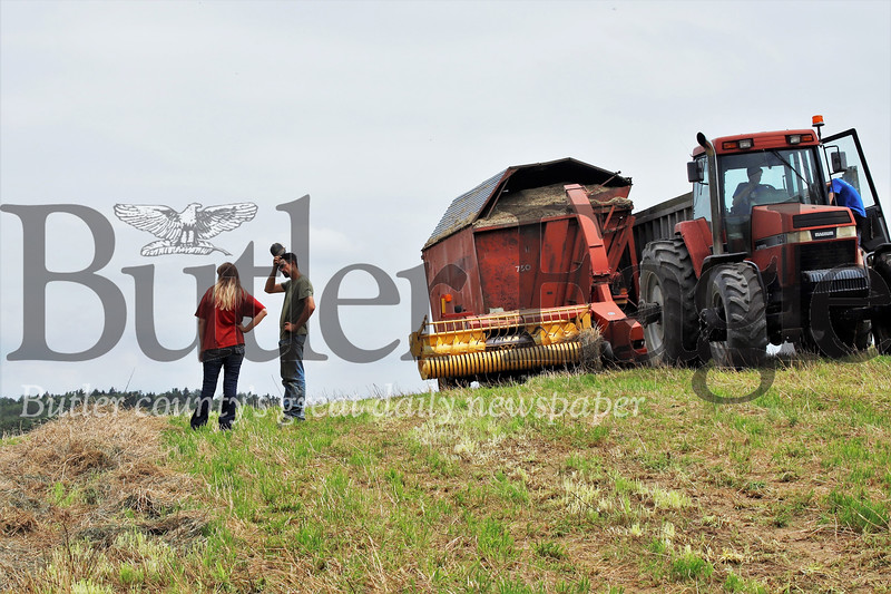Stacy and Brian Miller discuss the day's plans while their sons Garrett and Austin standby in one of the farm's tractors. Seb Foltz/Butler Eagle (Picture from July 2019)