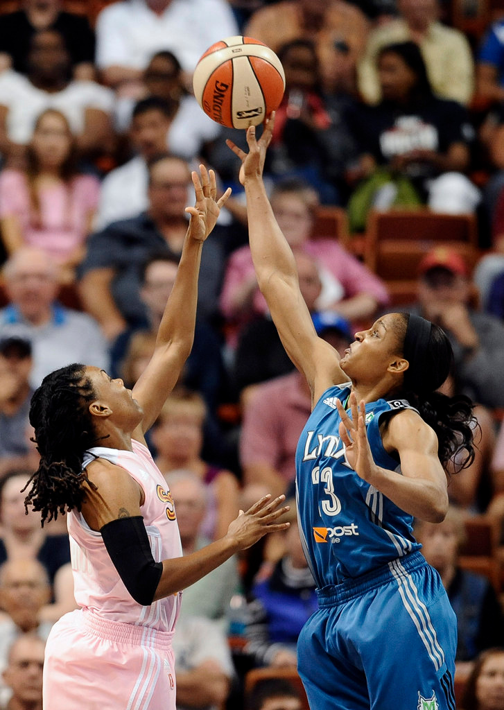 . Minnesota Lynx\'s Maya Moore, right, blocks a shot attempt by Connecticut Sun\'s Tan White, left, during the first half. (AP Photo/Jessica Hill)