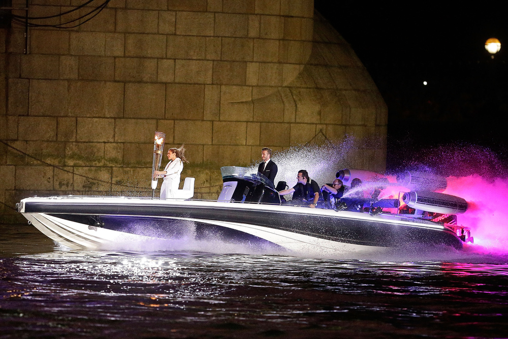 . David Beckham passes under Tower Bridge driving a speedboat named \'Max Power\' which carries the Olympic Torch carried by torchbearer Jade Bailey on July 27, 2012 in London, England. Athletes, heads of state and dignitaries from around the world have gathered in the Olympic Stadium for the opening ceremony of the 30th Olympiad. London plays host to the 2012 Olympic Games which will see 26 sports contested by 10,500 athletes over 17 days of competition. (Photo by Matthew Lloyd/Getty Images)