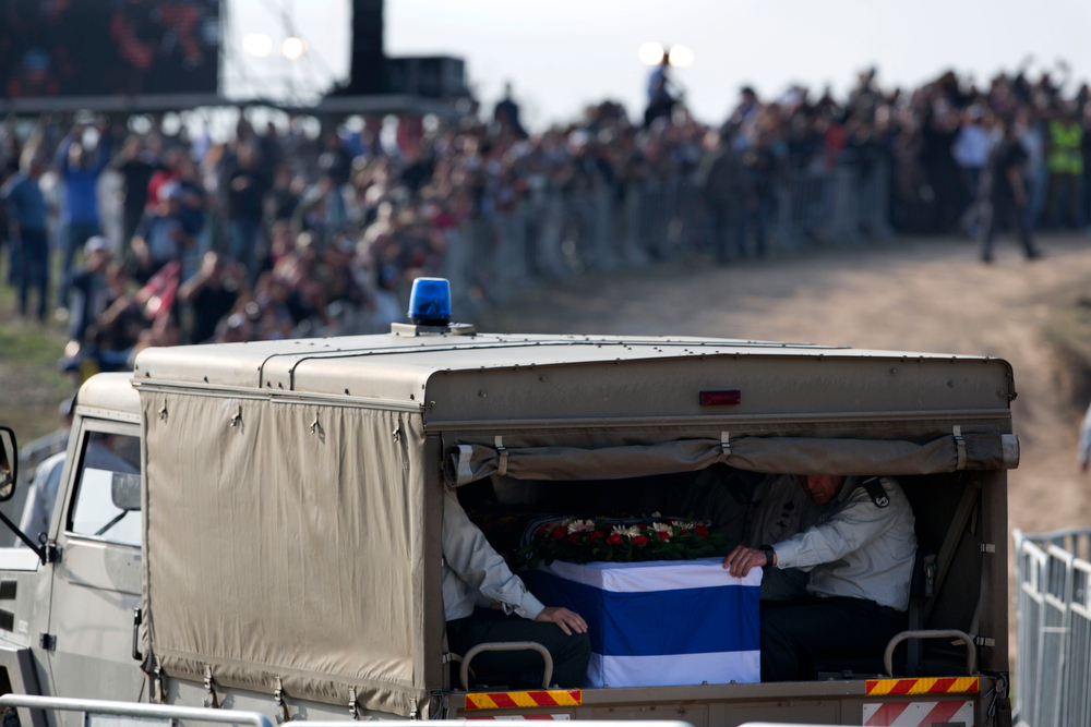 . Israelis line the route as a military vehicle carries the coffin of former Israeli Prime Minister Ariel Sharon during his funeral at his family farm, Havat Shikmim, in Southern Israel, Monday, Jan. 13, 2014. Israel said its final farewell to the late Ariel Sharon on Monday, staging a state ceremony outside the parliament building before taking his flag-draped coffin on a cross-country procession to its final resting place at his home in southern Israel. (AP Photo/Oded Balilty)