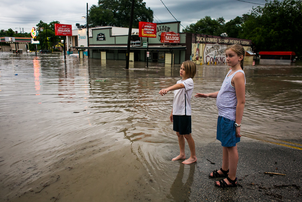 . AUSTIN, TX - MAY 25:   Murphy Canning and Annika Rolston watch as a street remains underwater from days of heavy rain on May 25, 2015 in Austin, Texas. Texas Gov. Greg Abbott toured the damage zone where one person is confirmed dead and at least 12 others missing in flooding along the Rio Blanco, which reports say rose as much as 40 feet in places, caused by more than 10 inches of rain over a four-day period. The governor earlier declared a state of emergency in 24 Texas counties.  (Photo by Drew Anthony Smith/Getty Images)