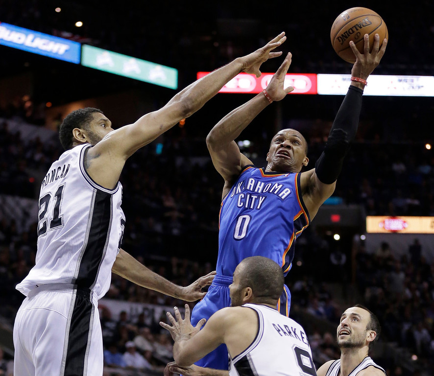 . Oklahoma City Thunder\'s Russell Westbrook (0) shoots over San Antonio Spurs\' Tim Duncan (21) and Tony Parker (9) during the second half of Game 1 of a Western Conference finals NBA basketball playoff series, Monday, May 19, 2014, in San Antonio. (AP Photo/Eric Gay)