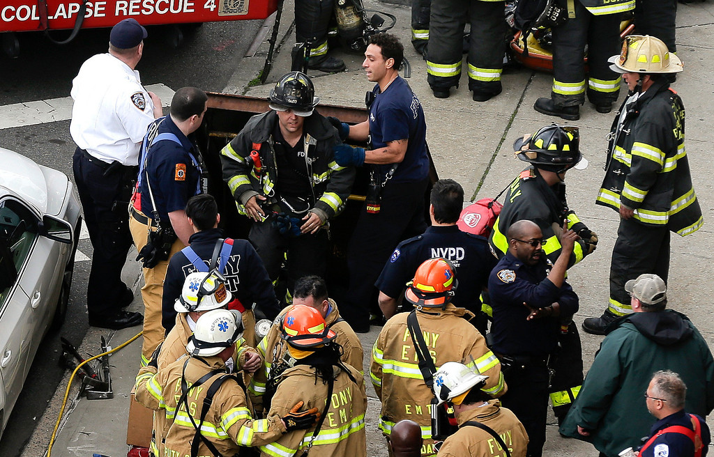 . New York City firefighters emerge from a hatch in the sidewalk at 60th Street and Broadway after evacuating passengers from a subway train that derailed in the Queens borough of New York, Friday, May 2, 2014.  The express F train was bound for Manhattan and Brooklyn when it derailed at 10:40 a.m. about 1,200 feet (365 meters) south of the 65th Street station, according to the Metropolitan Transportation Authority. Dozens of firefighters and paramedics with stretchers converged on Broadway and 60th Street, where passengers calmly left the tunnel through the sidewalk opening. A few were treated on stretchers. (AP Photo/Julie Jacobson)