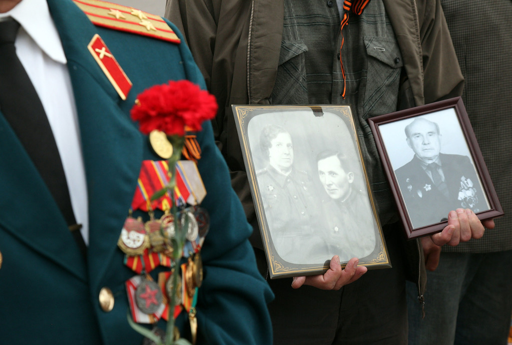 . A man holds pictures of dead relatives during a Victory Day ceremony at the Unknown Sailor Memorial in the southern Ukrainian city of Odessa on May 9, 2014.  AFP PHOTO/ ANATOLII  STEPANOV/AFP/Getty Images