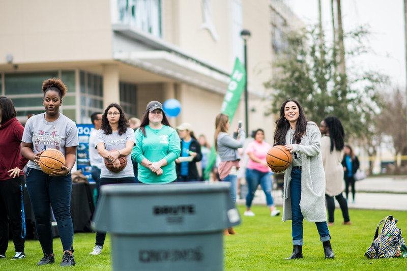 Jackeline Cardenas (right), prepares to throw a basketball into a garbage can during the 2018 Homecoming Tip Off Picnic on East Lawn.