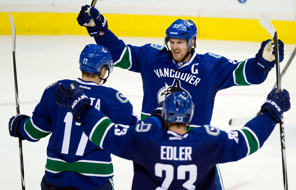. Vancouver Canucks\' Henrik Sedin, top, of Sweden, Radim Vrbata, left, of the Czech Republic, and Alexander Edler, of Sweden, celebrate Vrbata\'s goal against the Detroit Red Wings during the third period of an NHL hockey game in Vancouver, British Columbia on Saturday, Jan. 3, 2015. (AP Photo/The Canadian Press, Darryl Dyck)