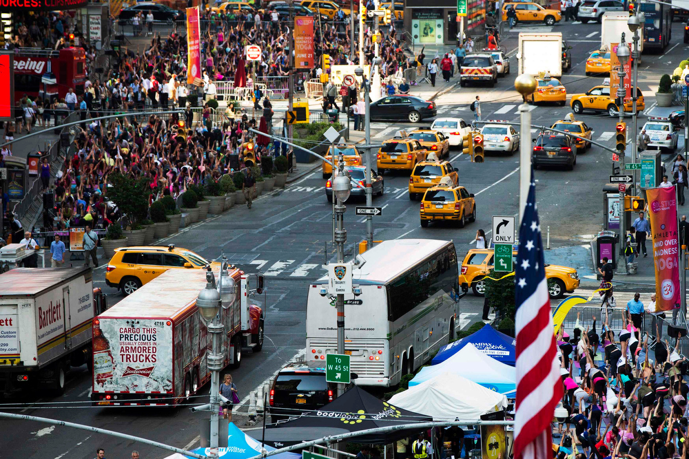 """. Traffic is pictured between groups of people taking part in a group yoga practice on the morning of the summer solstice in New York\'s Times Square, June 21, 2013. The \""""Solstice in Times Square\"""" event on Friday brought out thousands of participants to celebrate the year\'s longest day in New York. REUTERS/Lucas Jackson"""