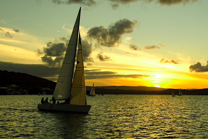 Yellow coloured stratocumulus cloud, sunset seascape over a sailboat.