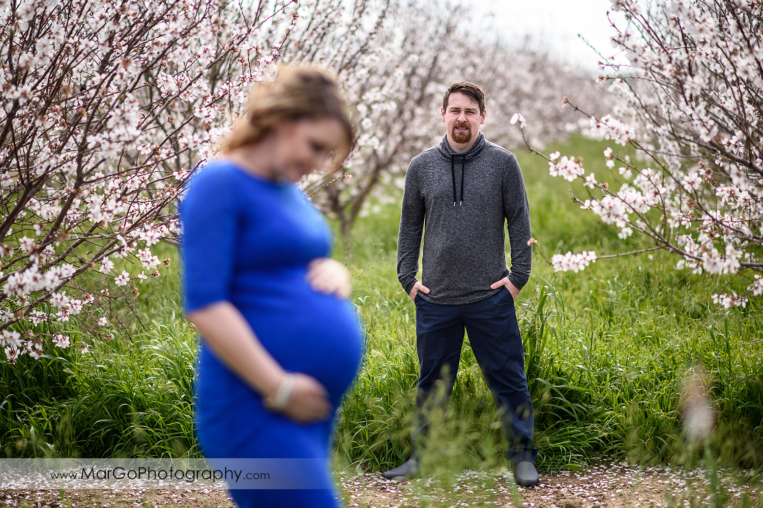 couple maternity session, focus on pregnant woman's husband, Tracy orchard