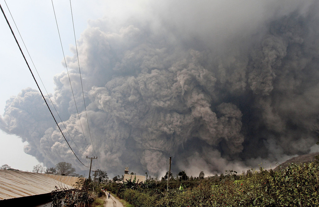 . Mount Sinabung releases pyroclastic flows during an eruption as seen from Namantaran, North Sumatra, Indonesia, Saturday, Feb. 1, 2014. (AP Photo)
