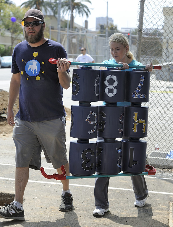 . LONG BEACH, CALIF. USA -- Brittany Tulkrabek and Aaron Kunkle carry a piece of play set during a one-day playground build at Edison Elementary School in Long Beach, Calif., on April 6, 2013.  More than 200 volunteers from the Long Beach Unified School District, Green Long Beach! and Zynga, joined organizers from KaBOOM! and residents to build a new playground at the Edison Child Development Center.  The playground is the fourth built by KaBOOM! and Zynga.org and is one of more than 150 playground builds KaBOOM! will lead across the country in 2013 in an effort to fulfill its vision of a great place to play within walking distance of every child in America. Photo by Jeff Gritchen / Los Angeles Newspaper Group