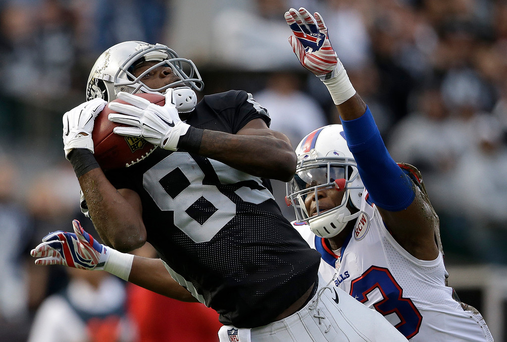 . Oakland Raiders wide receiver Kenbrell Thompkins (85) catches a 50-yard pass in front of Buffalo Bills cornerback Aaron Williams during the first quarter of an NFL football game in Oakland, Calif., Sunday, Dec. 21, 2014. (AP Photo/Marcio Jose Sanchez)