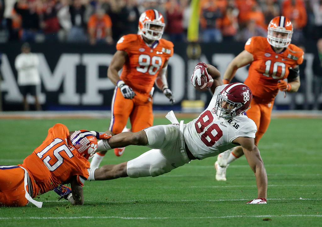 . Clemson\'s T.J. Green (15) tackles Alabama\'s O.J. Howard (88) during the first half of the NCAA college football playoff championship game Monday, Jan. 11, 2016, in Glendale, Ariz. (AP Photo/Chris Carlson)