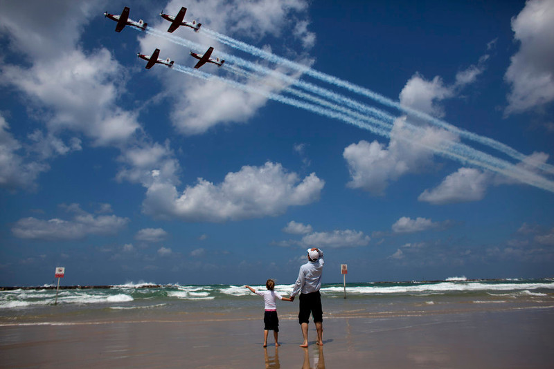 . Israelis watch an air show during Independence Day in Tel Aviv, Tuesday, April 16, 2013. Israel is celebrating its annual Independence Day, marking 65 years since the founding of the state in 1948. (AP Photo/Dusan Vranic)