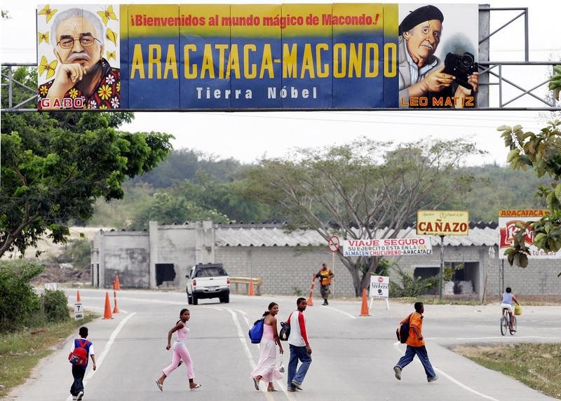 """. In this Jan. 4, 2006 file photo, people pass under a billboard that reads in Spanish \""""Welcome to the magical world of Macondo\"""" decorated with images of Colombian Nobel laureate Gabriel Garcia Marquez at the entrance of Marquez\'s hometown of Aracataca, Colombia. Marquez died on Thursday, April 17, 2014 at his home in Mexico City.  (AP Photo/Fernando Vergara, File)"""