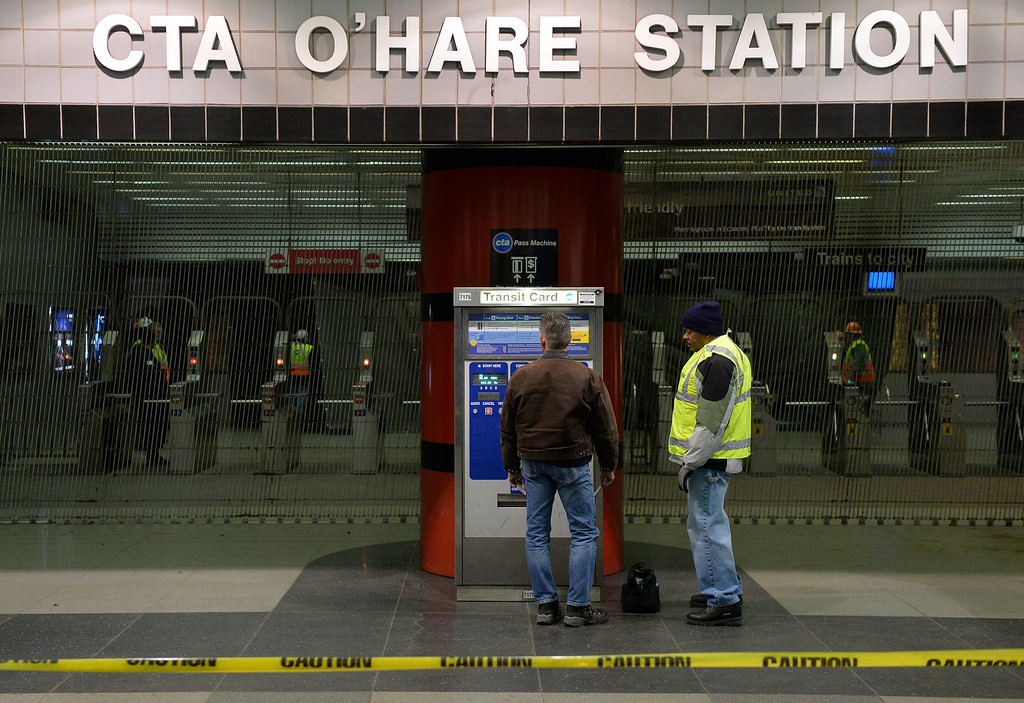. Chicago Transit Authority workers stand outside the O\'Hare International Airport station where a commuter train derailed at on March 24, 2014 in Chicago, Illinois. More than 30 were injured when the train slammed into the platform overnight coming to rest on an escalator.  (Photo by Brian Kersey/Getty Images)