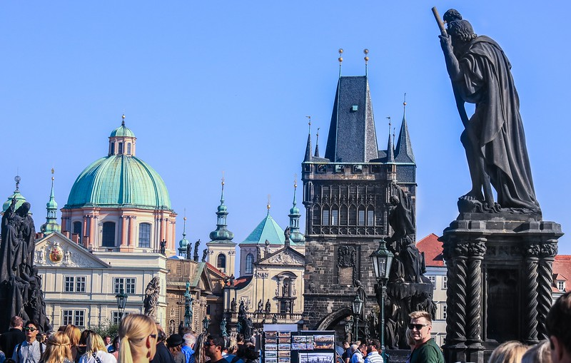Daytime on the ancient Charles Bridge in Prague. There are 30 statues on the bridge, most of them black (and, frankly, evil looking).