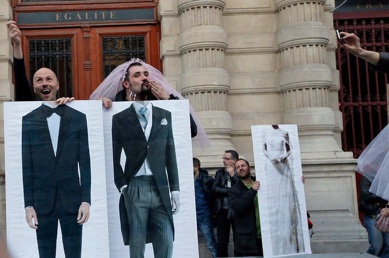 . Pro-gay marriage activists pose during a gathering at Paris 4th district city hall after French lawmakers legalized same-sex marriage, Tuesday, April 23, 2013 in Paris. Lawmakers legalized same-sex marriage after months of debate and street protests that brought hundreds of thousands to Paris. Tuesday\'s 331-225 vote came in the Socialist majority National Assembly. France\'s justice minister, Christiane Taubira, said the first weddings could be as soon as June. (AP Photo/Francois Mori)