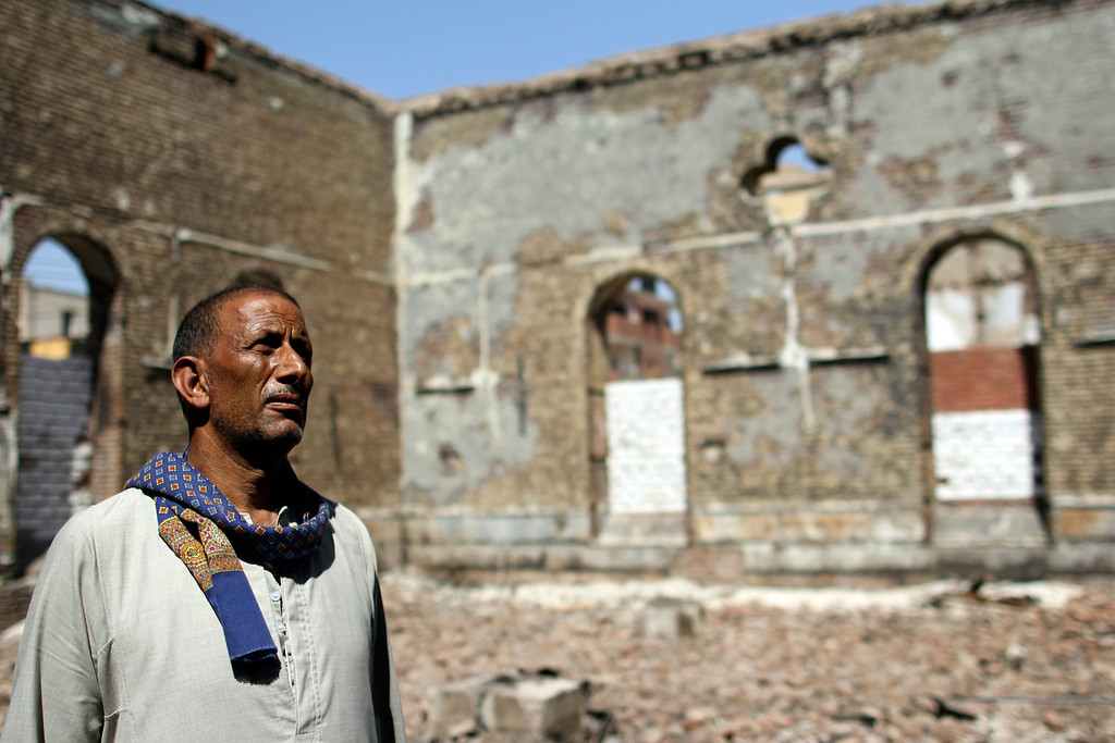 . In this Sept. 3, 2013 photo, a guard  looks at the ruins of the Evangelical Church of Malawi that was looted and burned by Islamists in Malawi, Minya province, Egypt. With the army and police already fighting a burgeoning militant insurgency in the Sinai Peninsula, there are growing signs that a second insurgency could erupt in the south _ particularly in Minya and Assiut provinces, both Islamist strongholds and both home to Egypt\'s two largest Christian communities. (AP Photo/El Shorouk Newspaper, Roger Anis)