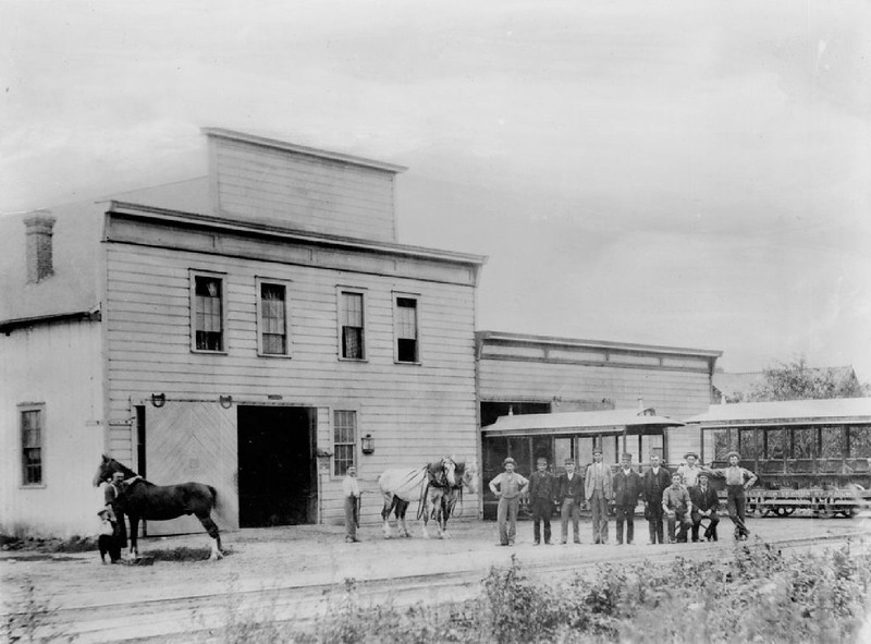 Portrait of men standing outside of a Vernon Street Railway Car barn on the corner of 22nd Street and Central Avenue, Los Angeles, ca.1890