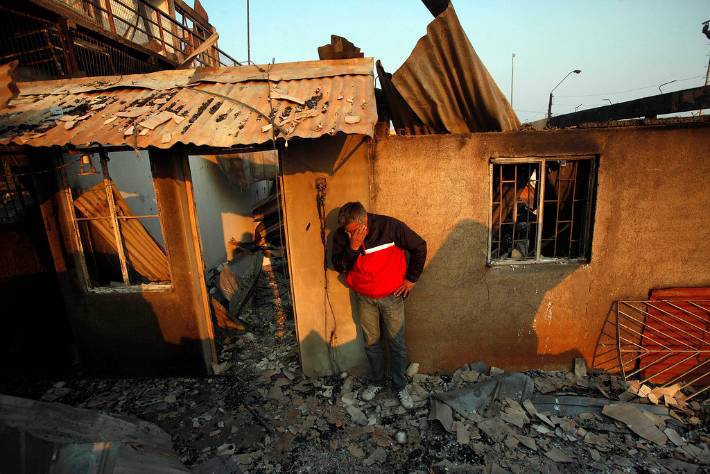 . A man cries next to the remains of his house after a forest fire destroyed it in Valparaiso, Sunday April 13, 2014. Authorities say the fires have destroyed hundreds of homes, forced the evacuation of thousands and claimed the lives of at least seven people.  ( AP Photo/ Luis Hidalgo)
