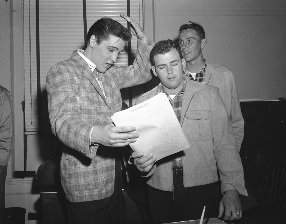. Elvis Presley, left, 23-year-old rock and roll singer, gestures at his short hair as he chats with a former school chum, Farley Gey, 22, who is entering the Army with Elvis, in Memphis, March 24, 1958. Robert Maharrey, 22, another inductee, looks on from the rear. The scene took place at the local draft board headquarters. (AP Photo/Fred J. Griffith)