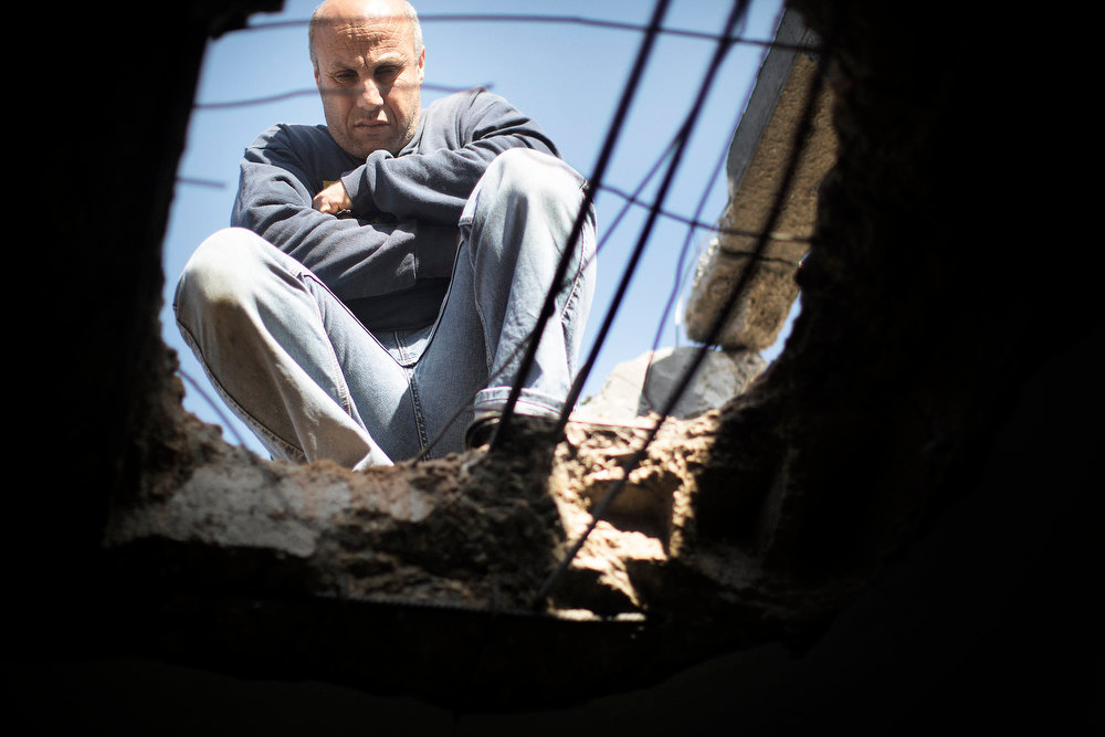 Description of . A Palestinian man squats while looking through a hole in the roof of the from the Tatari family home in Jabalia, northern Gaza Strip, damaged following Israeli strikes, on November 13, 2012. Israeli Defence Minister Ehud Barak warned that a flare-up in violence with Gaza was