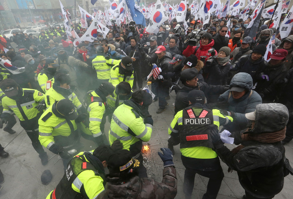 ". Protesters scuffle with police officers during a rally against North Korea\'s participation in the 2018 Pyeongchang Winter Olympics in Seoul, South Korea, Sunday, Feb. 11, 2018. A rare invitation to Pyongyang for South Korean President Moon Jae-in marked Day Two of the North Korean Kim dynasty\'s southern road tour, part of an accelerating diplomatic thaw that included some Korean liquor over lunch and the shared joy of watching a ""unified\"" Korea team play hockey at the Olympics. (AP Photo/Ahn Young-joon)"