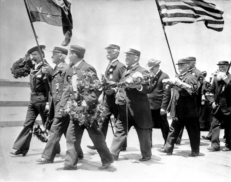 Naval veterans marching towards the ocean holding flowers during Memorial Day ceremonies, ca.1930