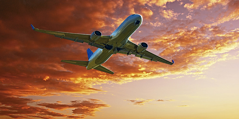 Jet Airliner Flying in an Orange colour Altocumulus cloudy sky. Australia.